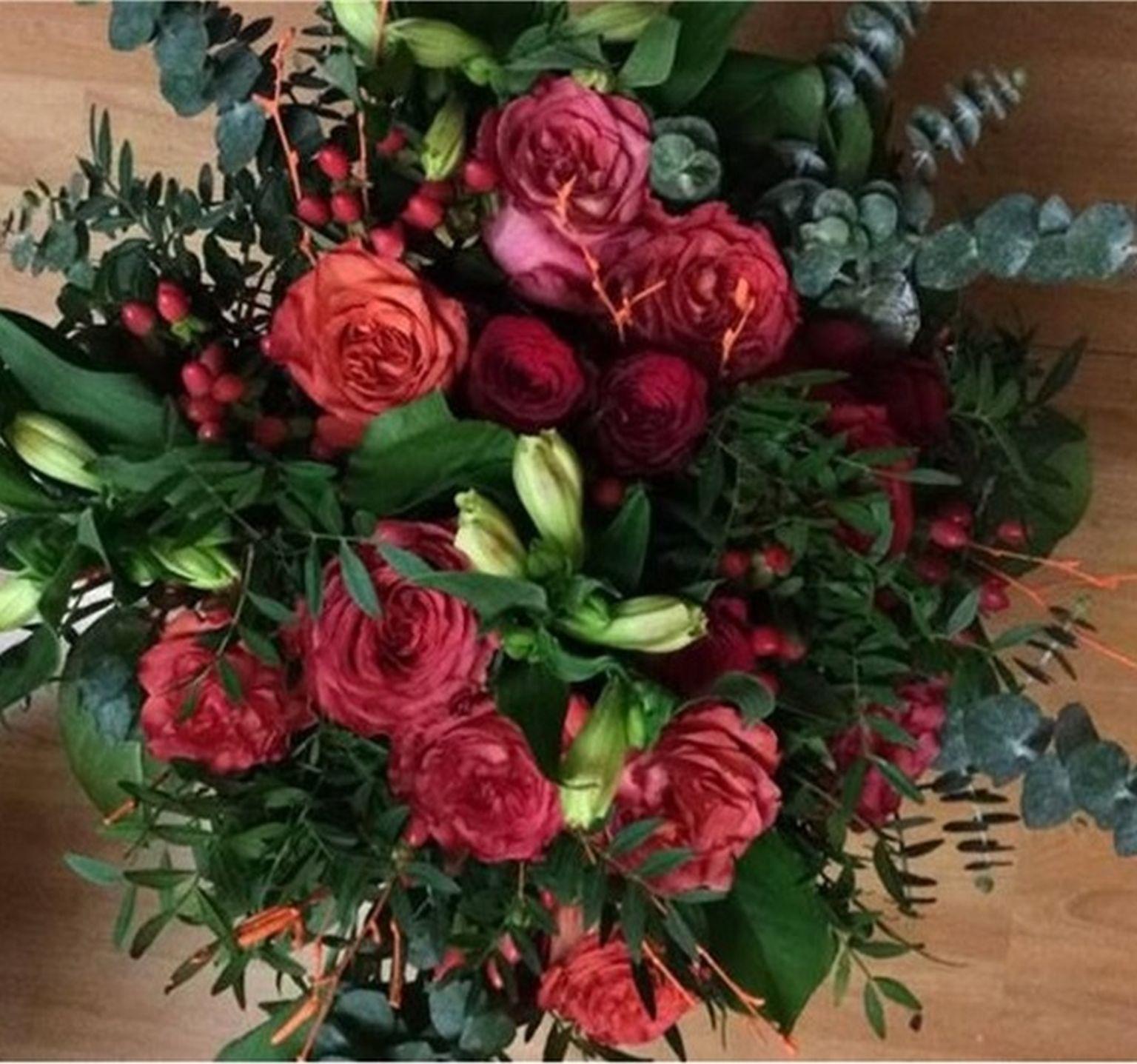 Kulatá kytice z oranžových a červených růží, alstromerie, hipericum, eukalypt, pistacie